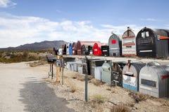 邮箱行在有山的沙漠在背景中 免版税库存图片