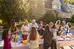 邻居在桌附近谈话并且吃在集团会议 图库摄影