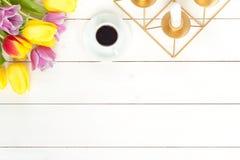 郁金香、coffe和蜡烛在白色木头 免版税库存照片