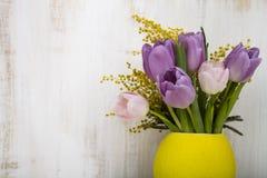 郁金香和含羞草花束在一个黄色花瓶在一木backgr 免版税库存照片