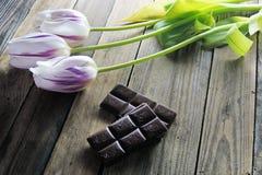 郁金香和巧克力在木背景 库存照片