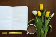 郁金香和心脏在一本书在一张木桌上 免版税库存照片