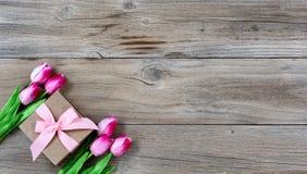 郁金香和礼物为在土气木背景的母亲节 免版税库存照片