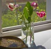 郁金香和铃兰在一个玻璃瓶子在村庄的窗台安置,点燃由太阳 免版税库存图片