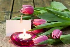 郁金香在花瓶和灼烧的蜡烛 免版税库存图片