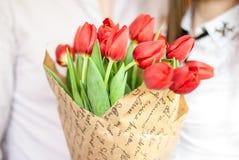 郁金香好的明亮的红色花束与年轻夫妇的在背景 免版税库存图片