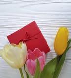 郁金香秀丽在白色木背景的春天日期,礼物盒花束  库存照片