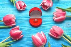 郁金香花和婚戒在礼物提出箱子在木背景 婚姻提供 提案 图库摄影