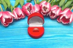 郁金香花和婚戒在礼物提出箱子在木背景 婚姻提供 提案 免版税库存照片