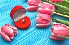 郁金香花和婚戒在礼物提出箱子在木背景 婚姻提供 提案 库存照片