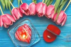 郁金香花和婚戒在礼物提出箱子在木背景 婚姻提供 提案 库存图片