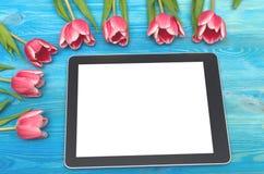 郁金香花和片剂计算机设备有黑屏的在木背景与拷贝空间 妇女天概念 免版税库存图片
