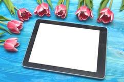 郁金香花和片剂计算机设备有黑屏的在木背景与拷贝空间 妇女天概念 免版税库存照片