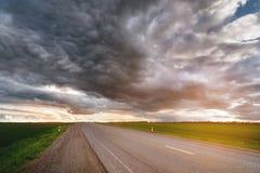 郊区柏油路风景有低织地不很细剧烈的云彩和绿色领域的在边 免版税库存图片