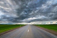 郊区柏油路风景有低织地不很细剧烈的云彩和绿色领域的在边 库存照片
