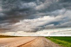 郊区柏油路风景有低织地不很细剧烈的云彩和绿色领域的在边 免版税库存照片