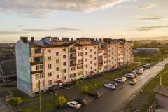 郊区风景,公寓 沿坏路的停放的汽车在天空蔚蓝拷贝空间背景的春日 免版税库存照片