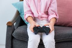 部份观点的与gamepad的孩子在打电子游戏的手上 库存图片
