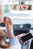 部份观点的有在手中运用唇膏一会儿的智能手机的女实业家 免版税库存照片