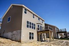 部分地完成的新的两层家建设中与乙烯基房屋板壁的细分的和窗口安装的和新的甲板 库存照片