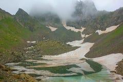部分地有一个山口的冻Didighali湖在一条供徒步旅行的小道的背景中在带领的高加索山脉变成银色L 图库摄影