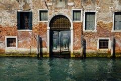 部分地有木葡萄酒门的生苔老砖房子门面在狭窄的运河在威尼斯,意大利 免版税图库摄影