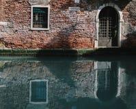 部分地有木葡萄酒门的生苔老砖房子门面在狭窄的运河在威尼斯,意大利 免版税库存照片