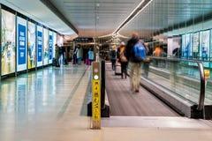 都伯林,爱尔兰–1月2019年都伯林机场,人们冲为他们的飞行的,有移动的走道的,行动迷离长的走廊 库存图片