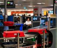 都伯林,爱尔兰,5月2019年都伯林机场终端1,手提行李扫描,检查行李的官员 免版税库存照片