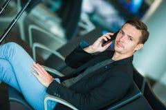 都市商人谈话在旅行里面在机场的巧妙的电话 偶然年轻商人佩带的衣服夹克 免版税库存图片