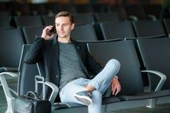 都市商人谈话在旅行里面在机场的巧妙的电话 偶然年轻商人佩带的衣服夹克 库存照片