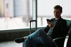 都市商人谈话在旅行里面在机场的巧妙的电话 偶然年轻商人佩带的衣服夹克 免版税图库摄影