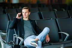 都市商人谈话在旅行里面在机场的巧妙的电话 有手机的年轻人在机场等待 库存图片