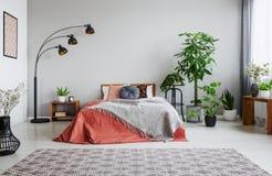 都市密林在有双人床、灯和地毯的卧室 库存照片
