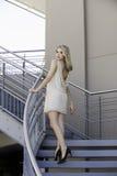 都市楼梯的可爱的白肤金发的妇女 免版税库存图片