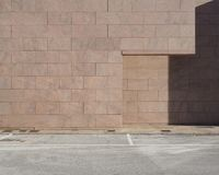 都市的背景 在桃红色石头大厦前面的混凝土路由块做成 库存照片