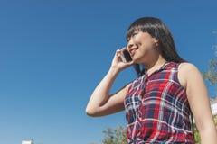 都市聪明的偶然年轻亚裔妇女谈话在智能手机 库存图片
