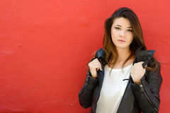 都市背景佩带的皮革jac的美丽的日本妇女 免版税库存照片
