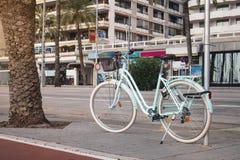 都市自行车租务在帕尔马的西班牙 有一个篮子的减速火箭的自行车在城市的背景 图库摄影
