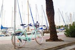 都市自行车租务在帕尔马的西班牙 有一个篮子的减速火箭的自行车在城市的背景 免版税库存照片