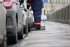 都市街道清洗的清扫的过程 有笤帚和尘土平底锅的工作者 库存照片
