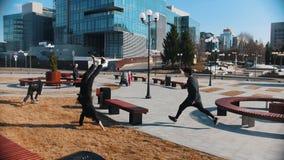 都市街道 跑在公园和克服长凳的三个人 影视素材