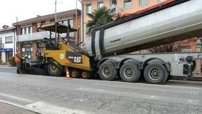 都市路建设中,涂柏油过程中 有一把铁锹的工作者在蓝色和橙色制服 股票录像