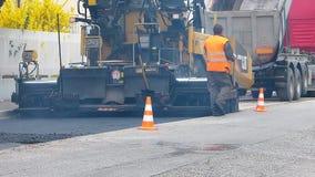都市路建设中,涂柏油过程中 有一把铁锹的工作者在蓝色和橙色制服 影视素材