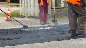 都市路建设中,涂柏油过程中 有一把铁锹的工作者在蓝色和橙色制服 股票视频