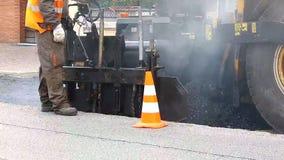 都市路建设中,涂柏油过程中 橙色制服的工作者 影视素材