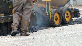 都市路建设中,涂柏油过程中 橙色制服的工作者 股票录像