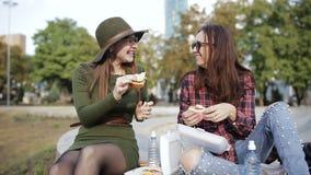 都市野餐在公园 两个女孩行家谈话和吃三明治 假日三明治 股票视频