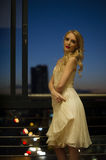 都市阳台的美丽的白肤金发的妇女 库存图片