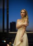 都市阳台的美丽的白肤金发的妇女 免版税库存照片